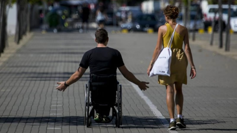 Mozo en cadeira de rodas acompañado da súa asistente persoal
