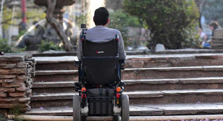 Home en cadeira de rodas fronte uns chanzos